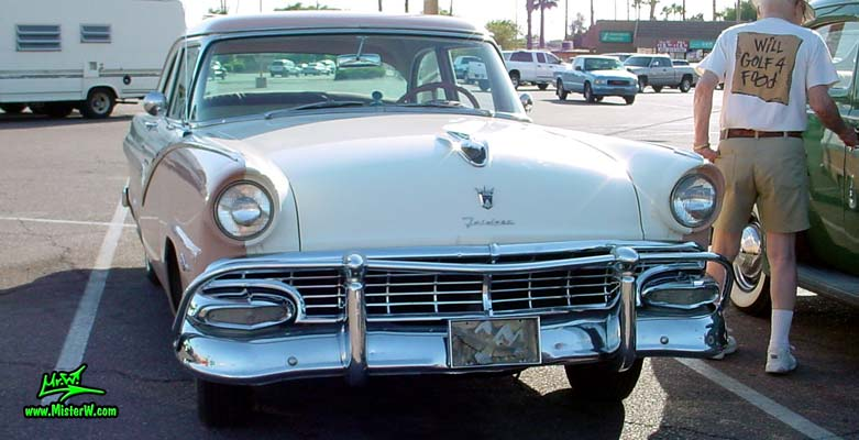 Photo of a white & pink 1956 Ford Fairlane 2 Door Post Club Sedan at a classic car meeting in Phoenix, Arizona. Frontview of a 56 Ford Fairlane Club Sedan