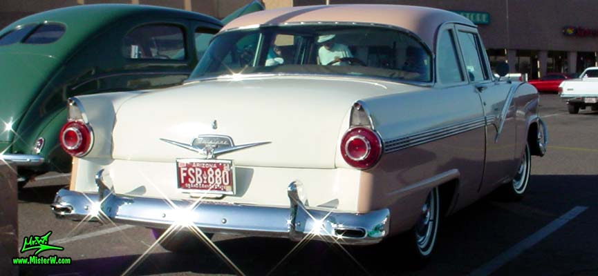 Photo of a white & pink 1956 Ford Fairlane 2 Door Post Club Sedan at a classic car meeting in Phoenix, Arizona. Rearview of a 56 Ford Fairlane Club Sedan