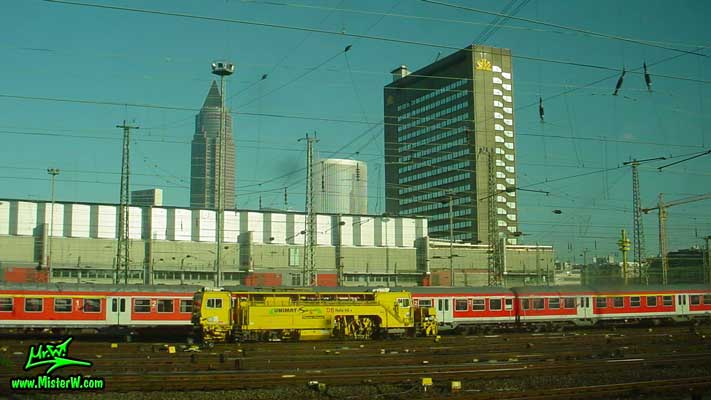 Photo of trains in front of the MesseTurm in downtown Frankfurt, taken from a ICE train Yellow Work Train in Frankfurt am Main