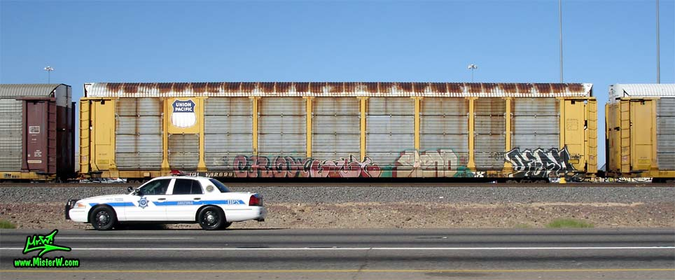 Photo of a Police Car in front of a Freight Train with Graffiti