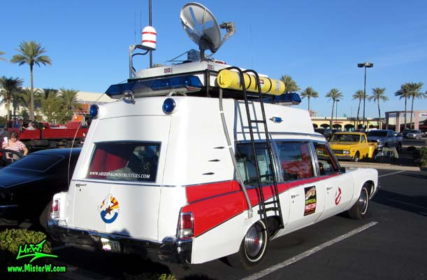 Photo of a red & white Pontiac Ambulance turned into ECTO-AZ the Arizona Ghostbusters Ectomobile at the Scottsdale Pavilions Classic Car Show in Arizona. Arizona Ghost Buster Ectomobile ECTO-AZ Roof Rack with Ghostbusters Equipment