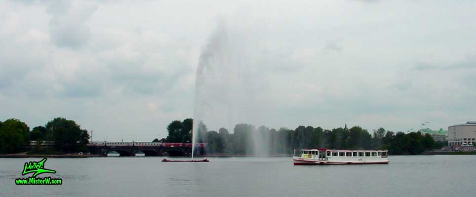 Photo of a Alster Dampfer (Tour Boat) passing the Fountain on the inner Alster lake (Binnen Alster), summer 2003 Alster Dampfer and Fountain in Hamburg