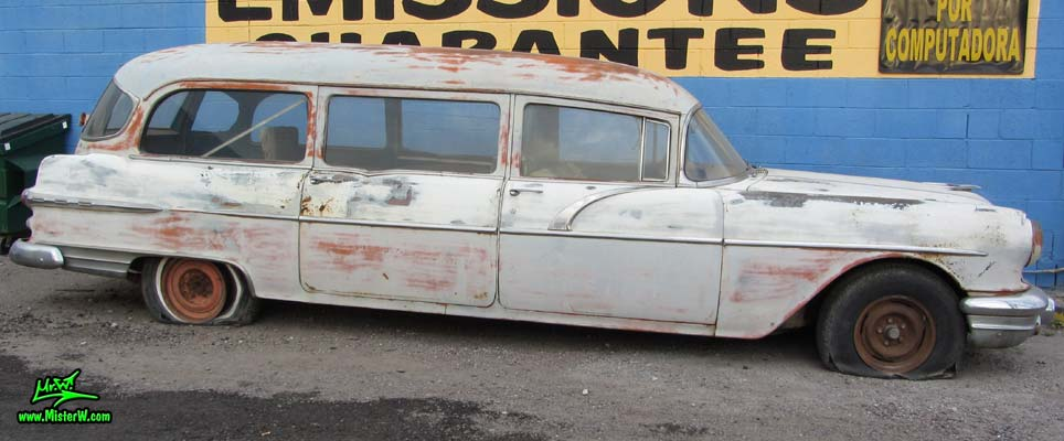 Photo of a faded grey 1956 Pontiac Memphian Ambulance in Phoenix, Arizona. Once painted red & white, in service for the Sheridan Willamina Fire Department in Oregon, build by the Memphian Coach Company in Memphis, Tennessee. Side view of a 1956 Pontiac Memphian Ambulance