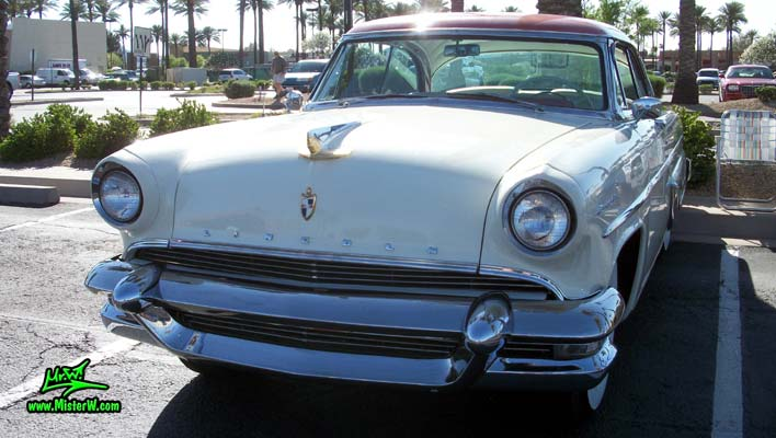 Photo of a white 1955 Lincoln Capri 2 door hardtop coupe at the Scottsdale Pavilions Classic Car Show in Arizona. Front view of a 1955 Lincoln Capri hardtop coupe