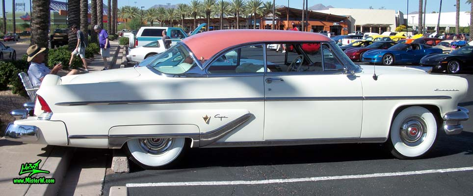 Photo of a white 1955 Lincoln Capri 2 door hardtop coupe at the Scottsdale Pavilions Classic Car Show in Arizona. Passenger's side of a 1955 Lincoln Capri hardtop coupe