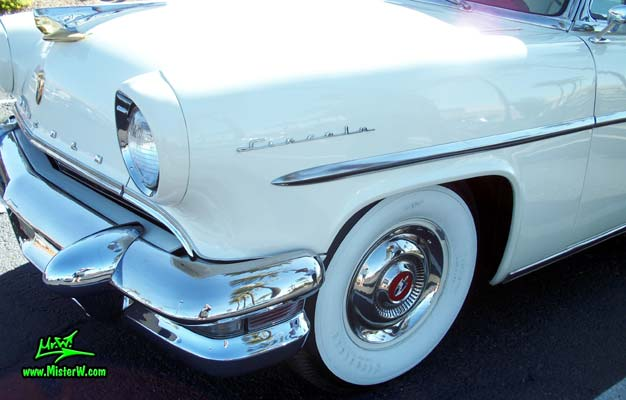 Photo of a white 1955 Lincoln Capri 2 door hardtop coupe at the Scottsdale Pavilions Classic Car Show in Arizona. Front chrome bumper & blinker of a 1955 Lincoln Capri hardtop coupe