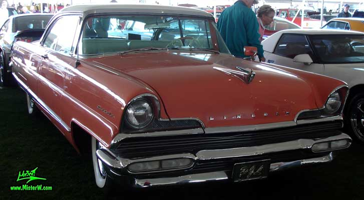 Photo of a pink 1956 Lincoln Premiere 2 door hardtop coupe at a Classic Car Auction in Scottsdale, Arizona. Frontview of a 1956 Lincoln Premiere