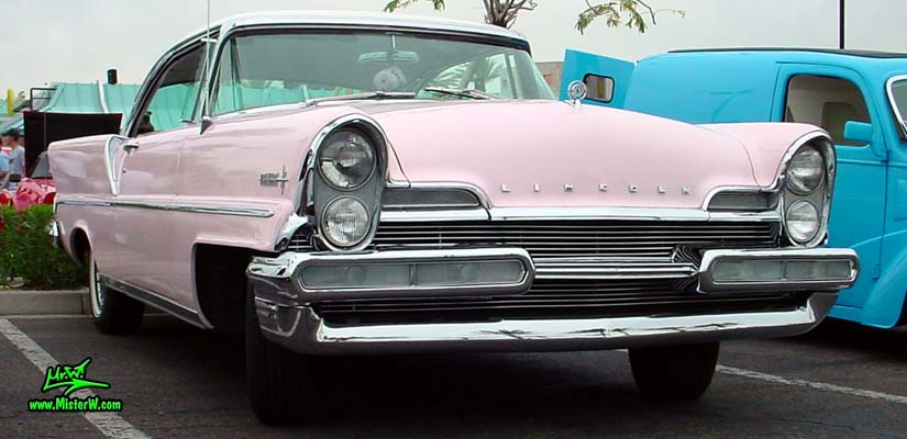 Photo of a pink & white 1957 Lincoln Premiere 2 door hardtop coupe at the Scottsdale Pavilions Classic Car Show in Arizona. Headlights of a 1957 Lincoln Premiere hardtop coupe