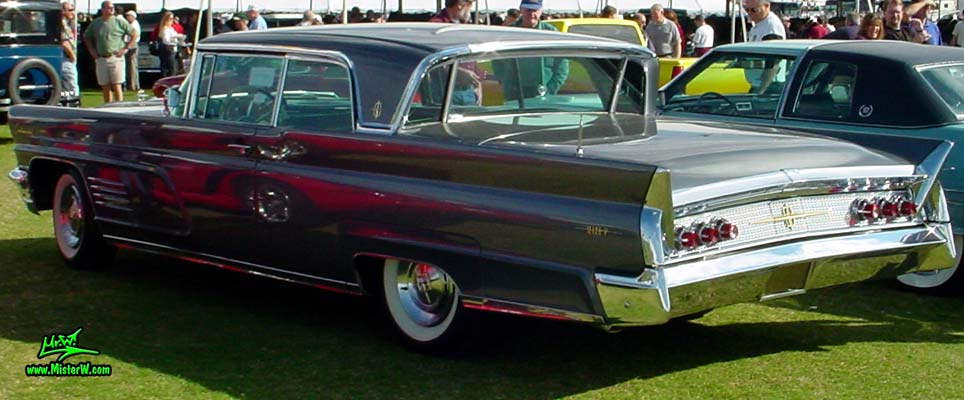 Photo of a silver gray metallic 1960 Lincoln Continental Mark V 2 door hardtop coupe at a Classic Car Auction in Scottsdale, Arizona. Side view of a 1960 Lincoln Continental Mark V coupe