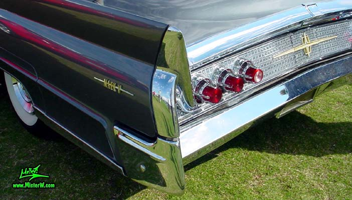 Photo of a silver gray metallic 1960 Lincoln Continental Mark V 2 door hardtop coupe at a Classic Car Auction in Scottsdale, Arizona. Tail lights & fin of a 1960 Lincoln Continental Mark V coupe