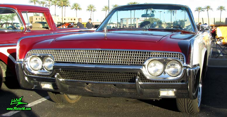 Photo of a red & white 1961 Lincoln Continental 4 door convertible at the Scottsdale Pavilions Classic Car Show in Arizona. Front chrome grill of a 1961 Lincoln Continental convertible