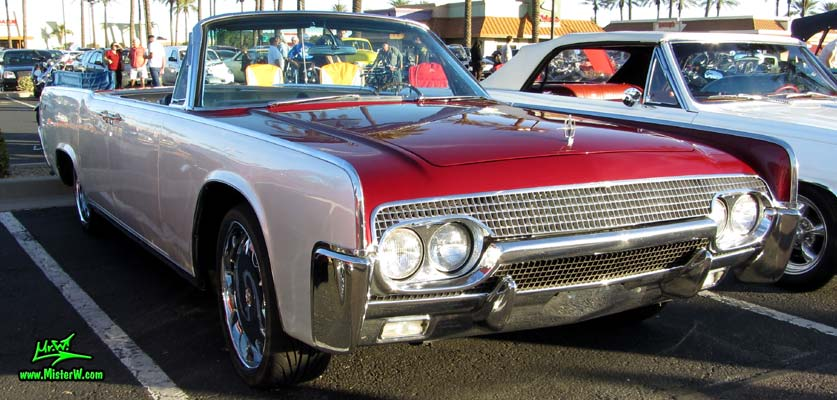 Photo of a red & white 1961 Lincoln Continental 4 door convertible at the Scottsdale Pavilions Classic Car Show in Arizona. Side view of a 1961 Lincoln Continental convertible