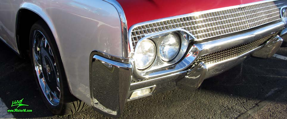 Photo of a red & white 1961 Lincoln Continental 4 door convertible at the Scottsdale Pavilions Classic Car Show in Arizona. Headlights & blinker of a 1961 Lincoln Continental convertible