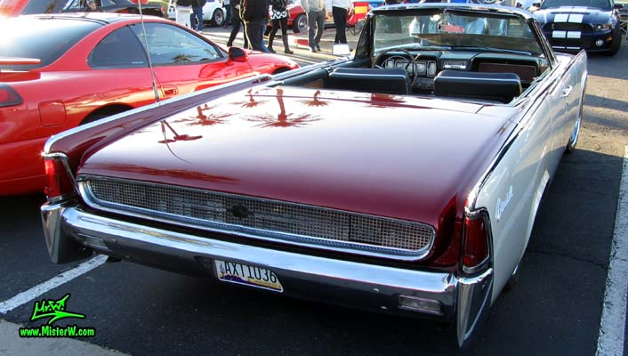 Photo of a red & white 1961 Lincoln Continental 4 door convertible at the Scottsdale Pavilions Classic Car Show in Arizona. Back of a 1961 Lincoln Continental convertible