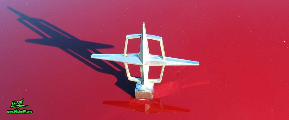 Photo of a red & white 1961 Lincoln Continental 4 door convertible at the Scottsdale Pavilions Classic Car Show in Arizona. Hood ornament of a 1961 Lincoln Continental convertible