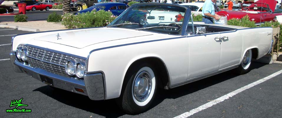 Photo of a white 1962 Lincoln Continental 4 door convertible at the Scottsdale Pavilions Classic Car Show in Arizona. 62 Lincoln Continental