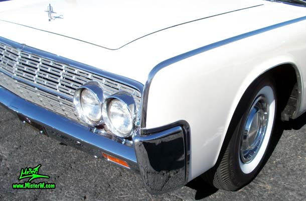 Photo of a white 1962 Lincoln Continental 4 door convertible at the Scottsdale Pavilions Classic Car Show in Arizona. Front fender of a 1962 Lincoln Continental convertible