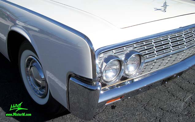 Photo of a white 1962 Lincoln Continental 4 door convertible at the Scottsdale Pavilions Classic Car Show in Arizona. Headlights & blimker of a 1962 Lincoln Continental convertible