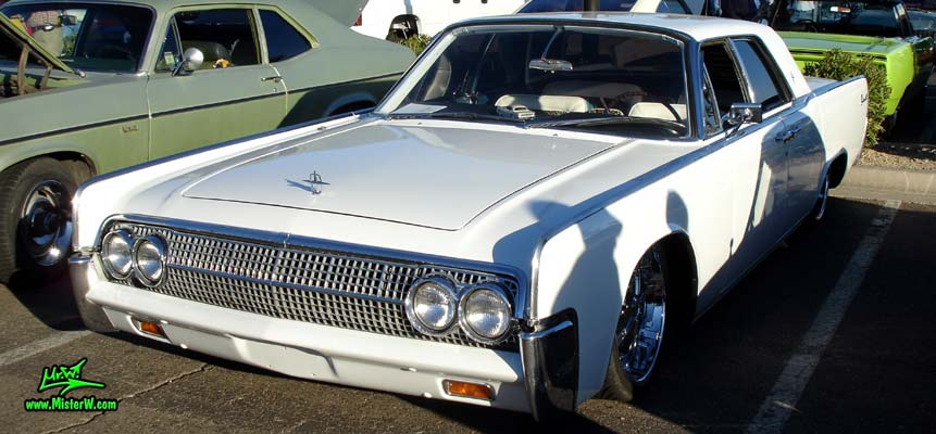 Photo of a white 1963 Lincoln Continental 4 door hardtop sedan at the Scottsdale Pavilions Classic Car Show in Arizona. Side view of a 1963 Lincoln Continental