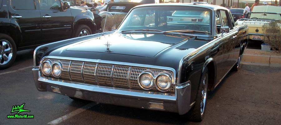 Photo of a black 1964 Lincoln Continental 4 door hardtop sedan at the Scottsdale Pavilions Classic Car Show in Arizona. Side view of a 1964 Lincoln Continental