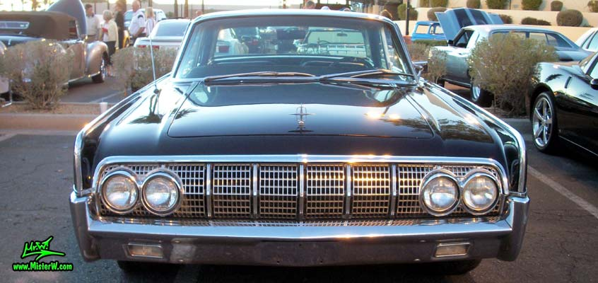 Photo of a black 1964 Lincoln Continental 4 door hardtop sedan at the Scottsdale Pavilions Classic Car Show in Arizona. Front view of a 1964 Lincoln Continental