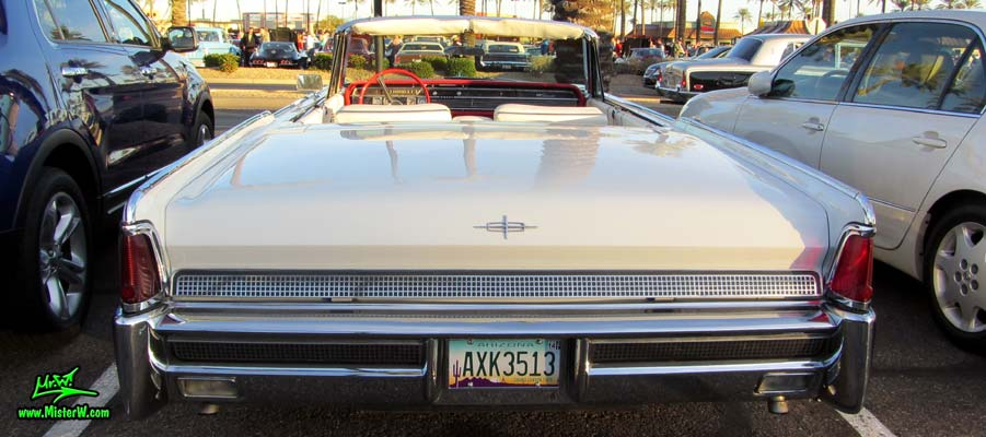 Photo of a white 1964 Lincoln Continental 4 door convertible at the Scottsdale Pavilions Classic Car Show in Arizona. Rear view of a 1964 Lincoln Continental convertible
