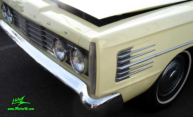 Photo of a tan & white 1965 Mercury 4 door sedan at the Scottsdale Pavilions Classic Car Show in Arizona. Headlights, blinker & chrome trim of a 1965 Mercury