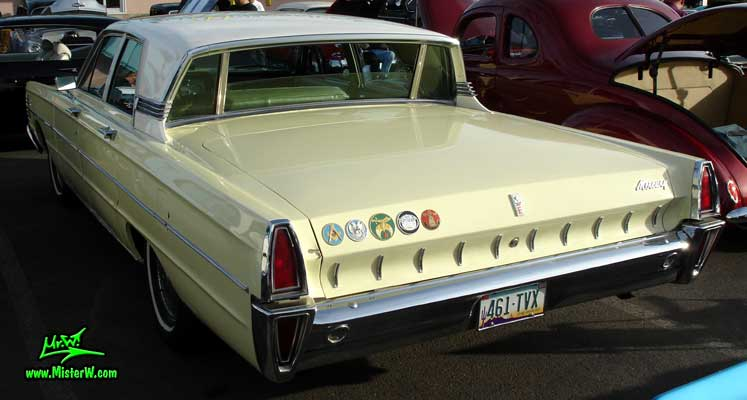 Photo of a tan & white 1965 Mercury 4 door sedan at the Scottsdale Pavilions Classic Car Show in Arizona. Rear view of a 1965 Mercury