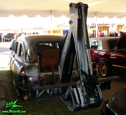 Photo of the Hearse Grave Digger a Monster Garage modified 54 Caddy with backhoe at a classic car auction in Scottsdale, Arizona. Rearview of Grave Digger the Monster Garage Hearse