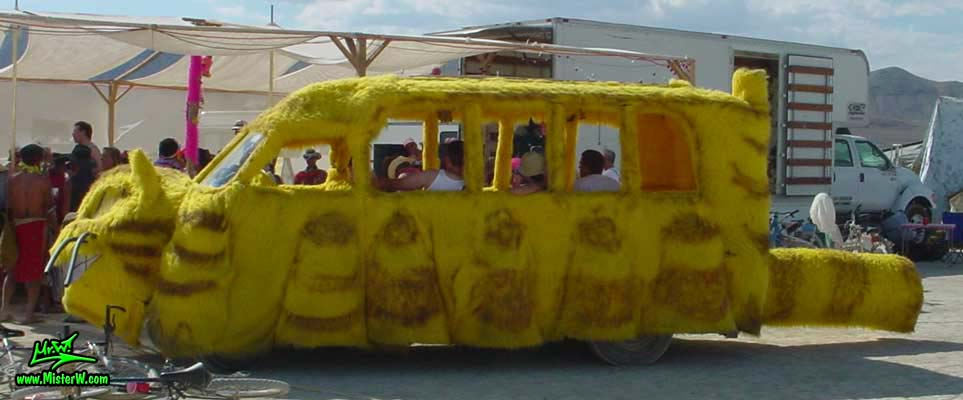 Photo of the furry yellow Cat Bus Mutant Vehicle / Art Car in Black Rock City, Nevada, 2002. Cat Bus Mutant Vehicle