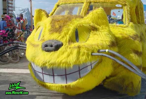 Photo of the furry yellow Cat Bus Mutant Vehicle / Art Car in Black Rock City, Nevada, 2002. Smiling Cat Bus Head