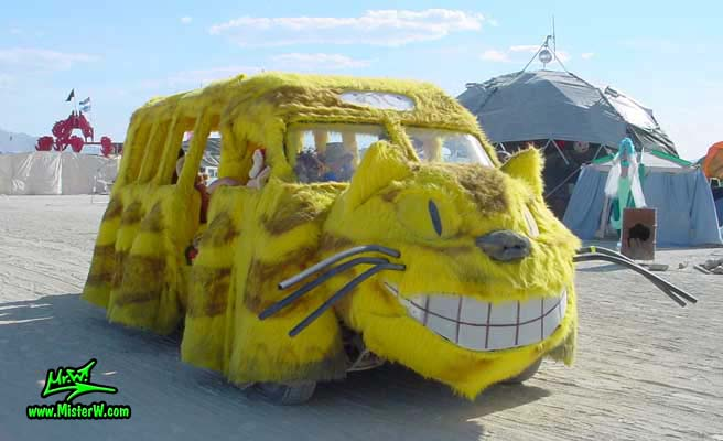 Photo of the furry yellow Cat Bus Mutant Vehicle / Art Car in Black Rock City, Nevada, 2002. Smiling Yellow Cat Bus Mutant Vehicle