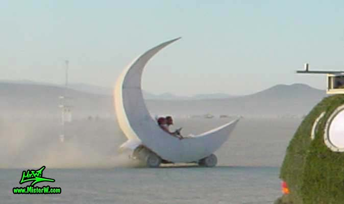 Photo of a white Moon Sickle Mutant Vehicle / Art Car in Black Rock City, Nevada, 2002. Moon Mutant Vehicle