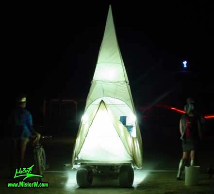 Photo of a illuminated white Moon Sickle Mutant Vehicle / Art Car at night in Black Rock City, Nevada, 2004. Moon Sickle Mutant Art Vehicle