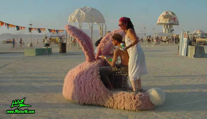 Photo of the giant electric powered Pink Bunny Slippers Mutant Vehicles / Art Cars in Black Rock City, Nevada, 2002. Drivable Pink Furry Bunny Slippers