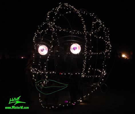 Photo of the illuminated Roving Head Mutant Vehicle / Art Car by Dale Huntsman at night in Black Rock City, Nevada, 2002. Roving Head Art Car