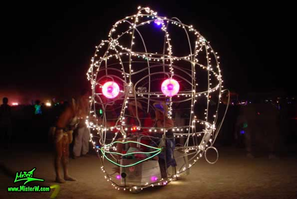 Photo of the illuminated Roving Head Mutant Vehicle / Art Car by Dale Huntsman at night in Black Rock City, Nevada, 2002. Roving Head Mutant Vehicle