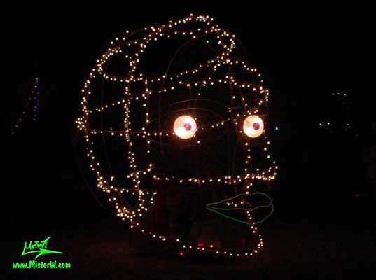 Photo of the illuminated Roving Head Mutant Vehicle / Art Car by Dale Huntsman at night in Black Rock City, Nevada, 2002. Giant Illuminated Roving Head Car