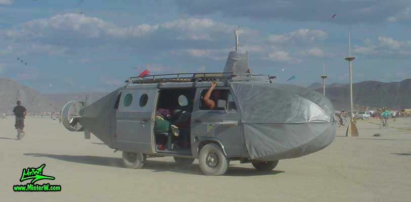 Photo of a silver Submarine Art VW Bus / Mutant Vehicle in Black Rock City, Nevada, 2002. Silver Submarine Bus