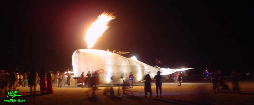 Photo of Moby Dick the giant illuminated & flamethrowing White Whale Mutant Vehicle / Art Car by Tom Kennedy at night in Black Rock City, Nevada, 2002. Giant Flamethrowing White Whale