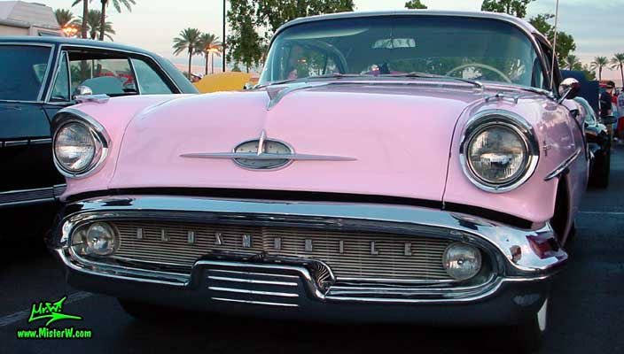 Photo of a pink 1957 Oldsmobile 2 Door Hardtop Coupe at the Scottsdale Pavilions Classic Car Show in Arizona. 57 Olds Coupe