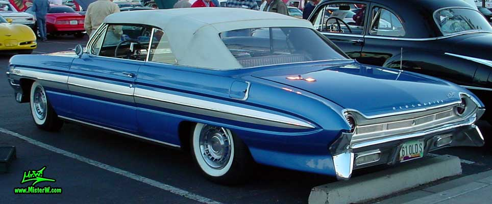 Photo of a blue metallic 1961 Oldsmobile Starfire 2 Door Convertible at the Scottsdale Pavilions Classic Car Show in Arizona. 1961 Oldsmobile with closed Convertible Top