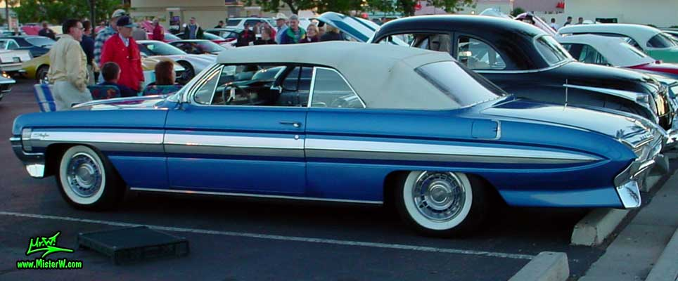 Photo of a blue metallic 1961 Oldsmobile Starfire 2 Door Convertible at the Scottsdale Pavilions Classic Car Show in Arizona. 1961 Oldsmobile Starfire Side Chrome