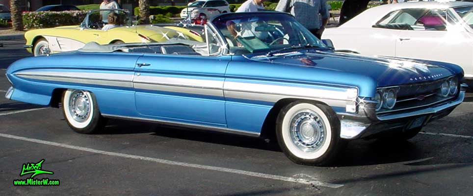 Photo of a blue metallic 1961 Oldsmobile Starfire 2 Door Convertible at the Scottsdale Pavilions Classic Car Show in Arizona. 1961 Oldsmobile Front & Side Chrome Trim