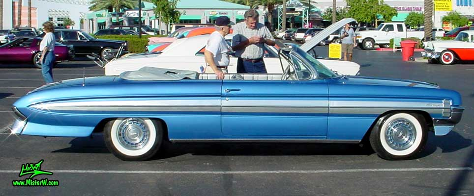 Photo of a blue metallic 1961 Oldsmobile Starfire 2 Door Convertible at the Scottsdale Pavilions Classic Car Show in Arizona. 1961 Oldsmobile Sideview