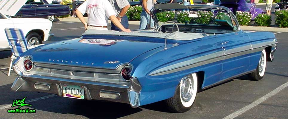 Photo of a blue metallic 1961 Oldsmobile Starfire 2 Door Convertible at the Scottsdale Pavilions Classic Car Show in Arizona. 1961 Oldsmobile Rear Bumper & Chrome
