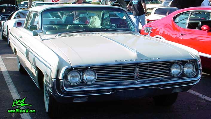 Photo of a white 1962 Oldsmobile Starfire 2 Door Hardtop Coupe at the Scottsdale Pavilions Classic Car Show in Arizona. 62 Olds Head Lights & Chrome Grill