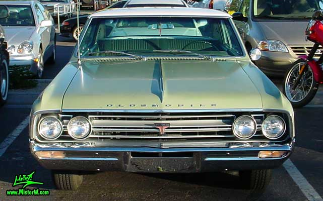Photo of a olive 1964 Oldsmobile 2 Door Hardtop Coupe at the Scottsdale Pavilions Classic Car Show in Arizona. 1964 Oldsmobile Head Lights & Chrome Grill