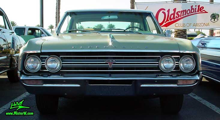 Photo of a olive 1964 Oldsmobile 2 Door Hardtop Coupe at the Scottsdale Pavilions Classic Car Show in Arizona. 1964 Oldsmobile Frontview