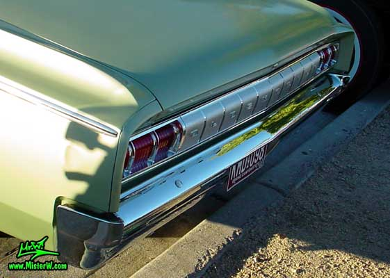 Photo of a olive 1964 Oldsmobile 2 Door Hardtop Coupe at the Scottsdale Pavilions Classic Car Show in Arizona. 1964 Oldsmobile Rear Bumper & Chrome